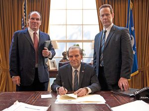 Harry Shearer as Richard Nixon sitting at desk in the oval office