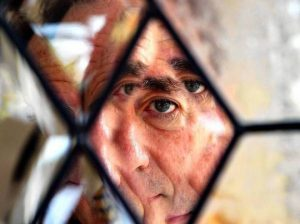 Harry Shearer looking through glass - photo by Genaro Molina